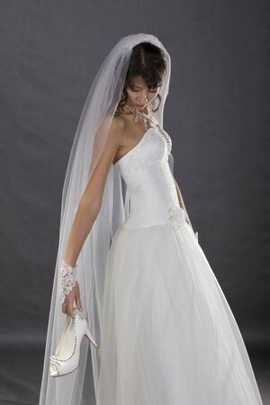 Young, beautiful bride posing in wedding clothe in studio