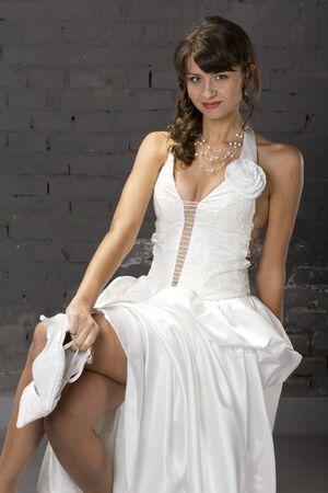 Young, beautiful bride posing in wedding dress before a brick wall