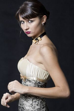 Young fashion model posing in studio, on dark background