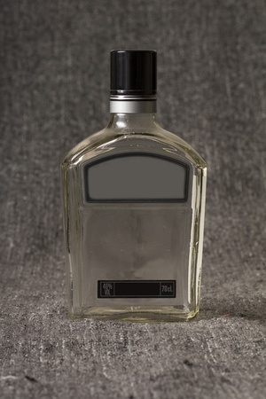 Empty bottle of whiskey or brandy on grey background photo