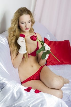 Sexy woman in lingerie, holding a rose, at valentines day Stock Photo