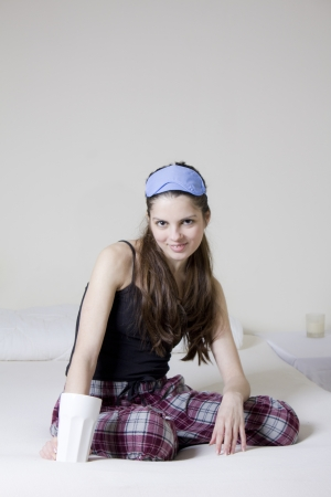 blinkers: Young woman in the bed, with a cup of tea and blinkers in her head