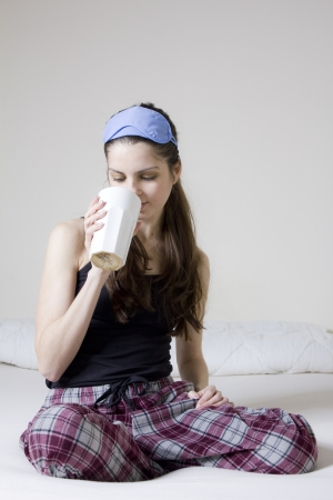 Young woman in the bed, with a cup of tea and blinkers in her head Stock Photo - 15492518