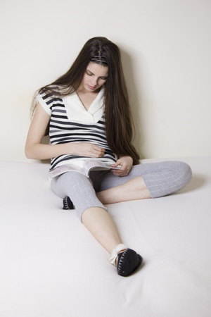 Young woman in bed rearding a fashion magazine photo