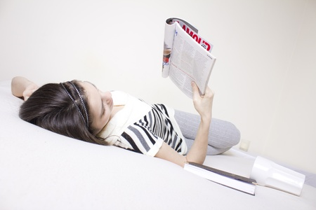 Young woman in bed rearding a fashion magazine Stock Photo