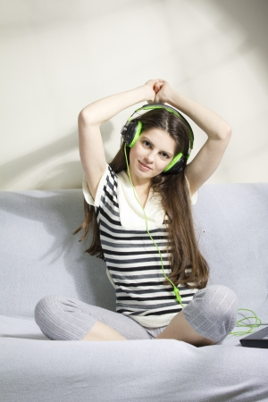 Young woman listening to music on the sofa, with headphone photo