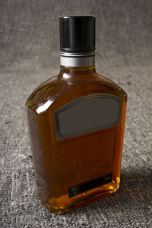 Full bottle of whiskey or brandy on grey background photo