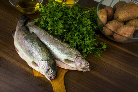 Two raw trouts on the kitchen table, ready to cook