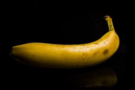 One fresh, yellow banana on black background with reflection