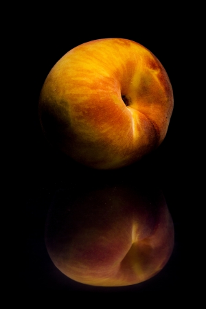 One fresh Peach on black background with reflection Stock Photo