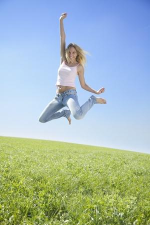 springende mensen: Jumping jonge vrouw te genieten van zon in de lente Stockfoto