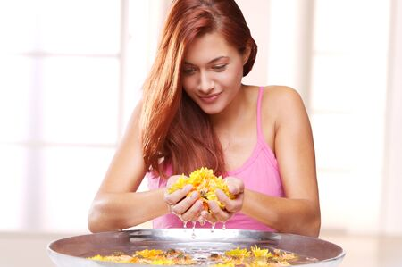 grown ups: Young Woman Holding Blossoms Over a Bowl with Water