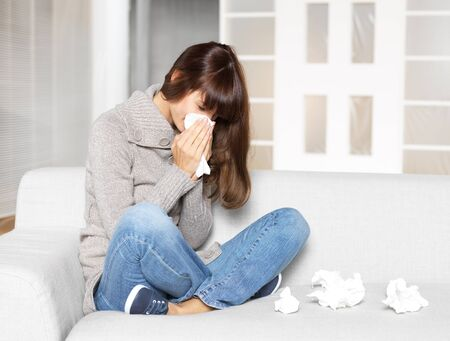 young woman is ill, blowing her nose Stock Photo - 11726628