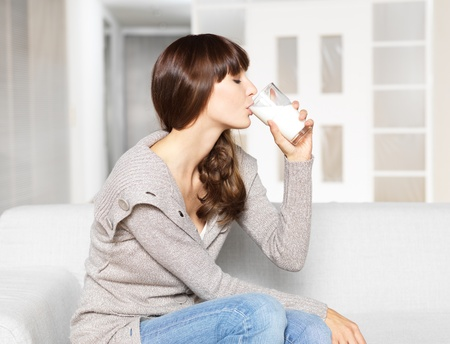 drinking milk: Young woman drinking glass of milk Stock Photo