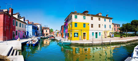 gaily: Venice, Burano island, small brightly-painted houses and channel with boats panorama