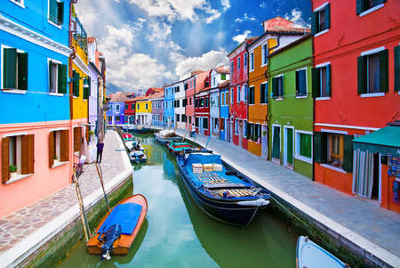 Venice, Burano island canal, small colored houses and the boats photo