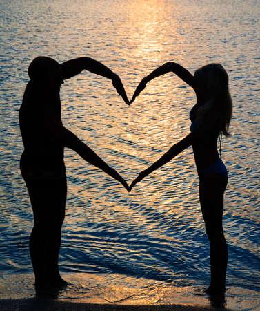 femme romantique: jeune couple faisant en forme de c?ur avec les bras sur la plage contre coucher de soleil dor�