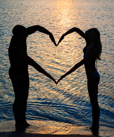 young couple making heart shape with arms on beach against golden sunset photo