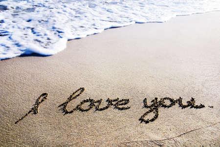 """te quiero: palabras """"Te amo"""" esbozo sobre la arena mojada con el brillo de onda Foto de archivo"""