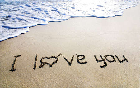 brilliance: words I love you outline on the wet sand with the wave brilliance Stock Photo