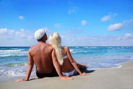 loving couple sitting on the sea sand beach and look at the blue sky Stock Photo