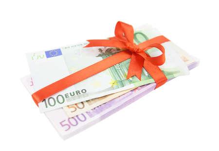 Die Euro-Geld Stapel mit einem Satin-rotem Band und Bogen isoliert auf weißem Hintergrund gebunden