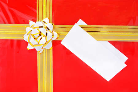 Single red gift box with golden ribbon and the close up of white card note photo