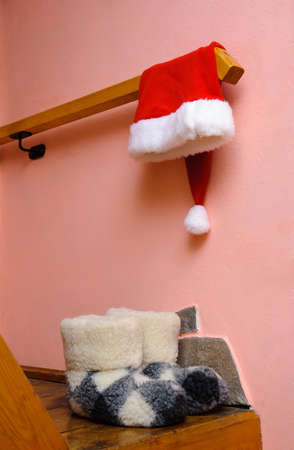 red santa hat and warm woolen  boots at home interior - christmas or new year's concept for postcard photo
