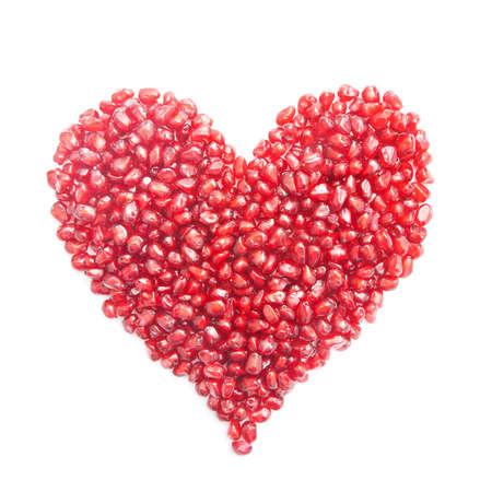 흰색 배경에 고립 된 심장의 형태에 잘 익은 석류 씨앗 - 개념을 사랑합니다