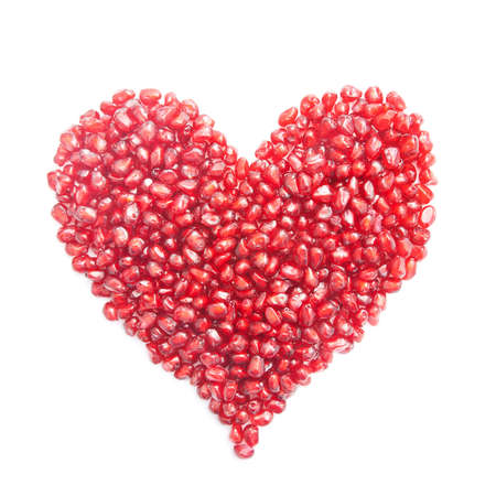 ripe pomegranate seeds in form of heart isolated on white background - love concept Stock Photo