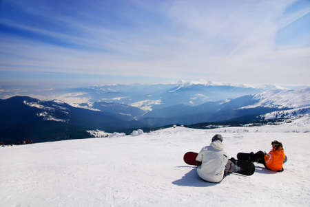 snowboarders sitting on anow and see at mountains photo