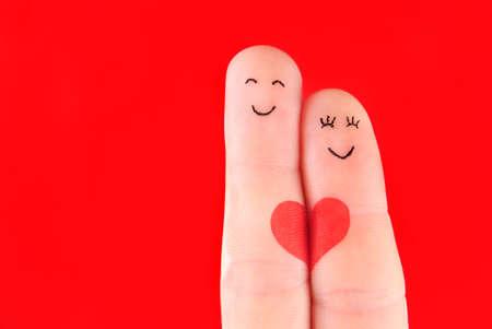 가족 개념 - 남자와 여자는 붉은 마음에 개최 손가락에서 그린 및 빨간색 배경에 고립