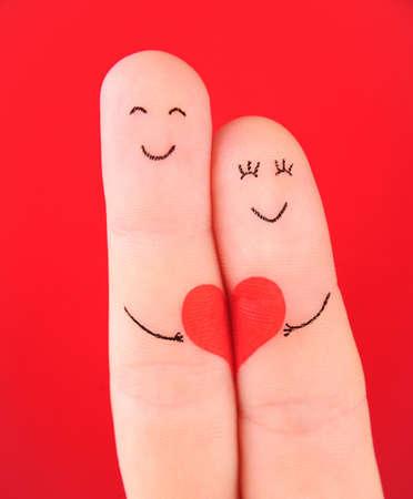 가족 개념 - 남자와 붉은 마음에 여자 보류는 손가락에 그린과 빨간색 배경에 고립