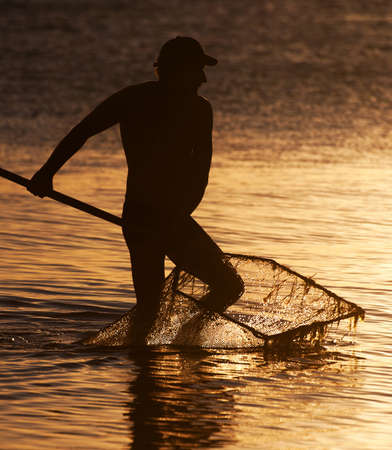 Fisherman with the landing net at sunset sea sunny way Stock Photo - 18259767