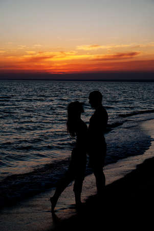beach kiss: Young couple silhouette on a sea beach on sunset background