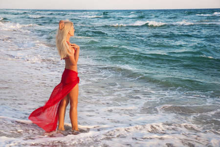 fidelidad: hermosa mujer esbelta joven rubia en falda roja y bikini en la playa del mar - concepto de espera romántica Foto de archivo