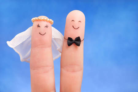 just married concept -  newlyweds painted at fingers against blue sky, good use for wedding invitation card Stock Photo