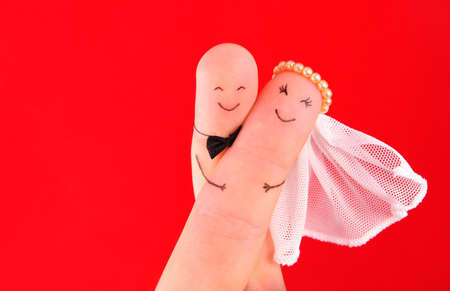 just married: pareja de recién casados, recién casados ??pintadas en los dedos contra el fondo rojo, el buen uso de la tarjeta de invitación de boda Foto de archivo