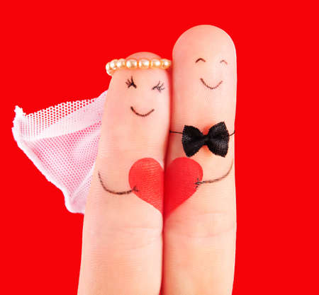 romantic man: wedding concept - newlyweds painted at fingers against red background Stock Photo
