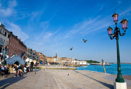 adriatic: picturesque seafront with flying doves and the street lamp in Venice, Italy in summer sunny day Stock Photo