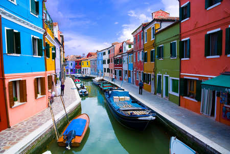 row of houses: Venice, Burano island canal, small colored houses and the boats Stock Photo