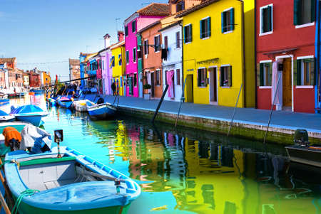 brightly colored: Venice, Burano island canal, small colored houses and the boat
