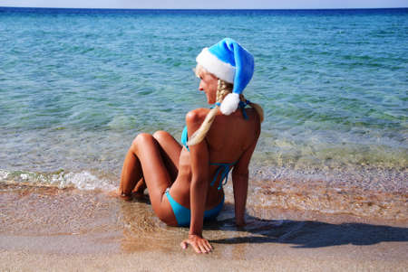 snow maiden: Beautiful woman in santa hat on the sand sea shore Stock Photo