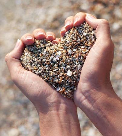 Handen die een zand in vorm van het hart