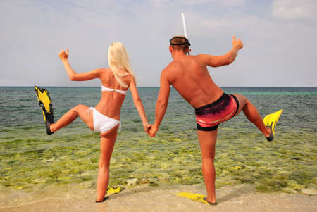 man and woman go to diving on summer beach photo