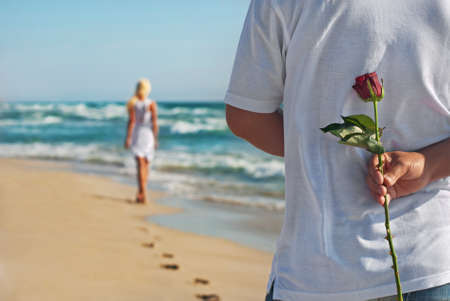 loving couple, man with rose waiting his woman on the sea beach at summer, the romantic, wedding or valentines day concept