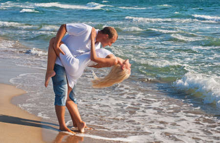 loving couple dancing on the sea beach at summer against sea waves