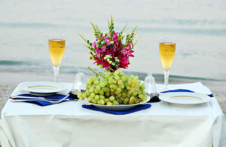 romantic dinner on the sea beach with candles and wine photo