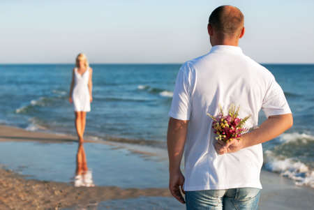 loving couple - man with flower bouquet waiting his woman on the sea beach at summer - the romantic dating or wedding or valentines day concept photo