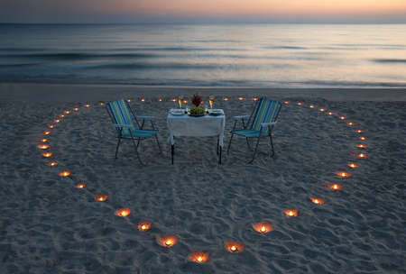 romantic dinner on the sea beach with candle heart in Maldives Stock Photo